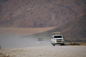 Staubwolke hinter Jeeps auf Schotterstraße in Namibia